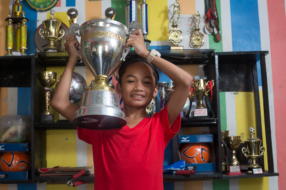 A young boy holding up his football trophy in a slum of Philippines