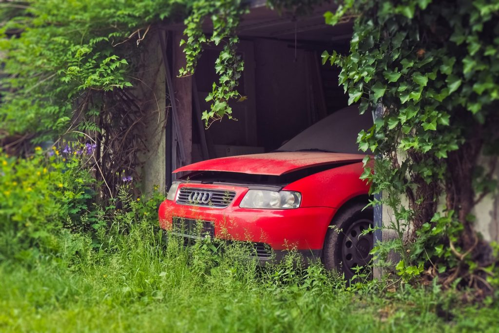 Abandoned red Audi car contributing to unfolding environmental disaster