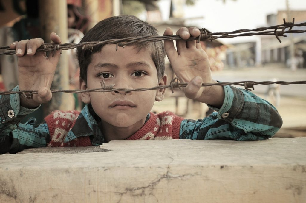 Indian child in poverty looking through barbed wire