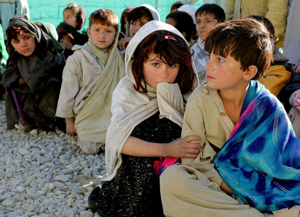 This photo displays a group of children in Afghanistan waiting for a food distribution delivered by a charity as part of their effort to meet the Sustainable Development Goals