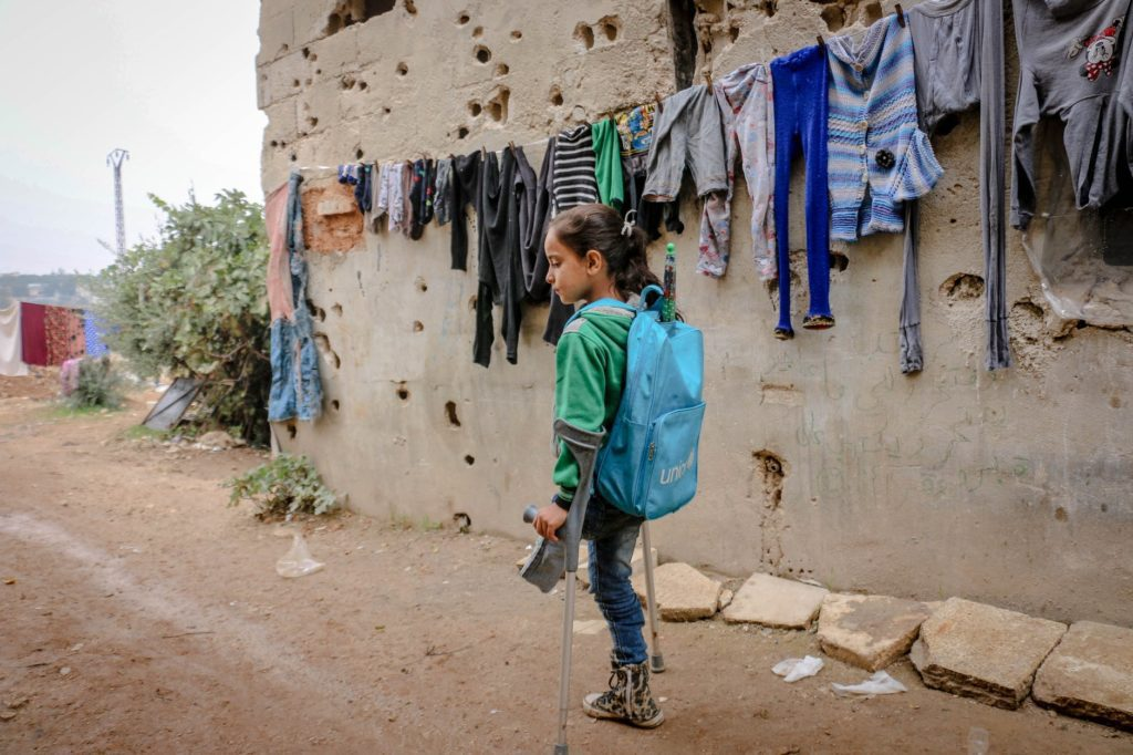 Disabled girl with one leg using crutches to move around in the street, wearing a unicef backpack